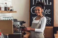 Afro American barista. Beautiful Afro American barista in apron is looking at camera and smiling while making coffee using a coffee machine royalty free stock image