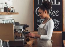 Afro American barista. Beautiful Afro American barista in apron is smiling while making coffee using a coffee machine royalty free stock photos