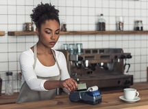 Afro American barista. Beautiful Afro American barista in apron is using a payment terminal while standing at bar counter royalty free stock photo