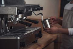 Afro American barista. Cropped image of Afro American barista in apron preparing coffee using a coffee machine Royalty Free Stock Photography