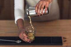 Afro American barista. Cropped image of beautiful Afro American barista in apron preparing a cocktail in shaker while standing at bar counter Royalty Free Stock Photography