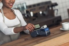 Afro American barista. Cropped image of beautiful Afro American barista in apron using a payment terminal and smiling while standing at bar counter stock photos