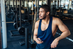 Afro american bodybuilder guy holding smartphone Stock Images