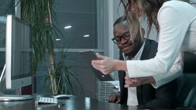 Afro-american boss and his asian secretary using digital tablet stock video footage