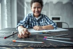 Afro American boy. Is drawing using colored pencils and smiling while sitting at the table at home, blurred, hand and some pencils in focus stock photos