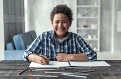 Afro American boy. Happy Afro American boy is drawing using colored pencils, looking at camera and smiling while sitting at the table at home stock photography