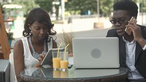 Afro-american business man and woman working together in modern cafe, having phone calls, using laptop and digital stock images