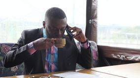 Afro american businessman is calling on smartphone and drinking coffee in cafe. Black guy is talking on smartphone. Afro american businessman is calling on stock footage