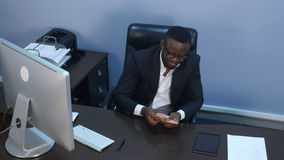 Afro-american businessman counts money, sitting in office Royalty Free Stock Photo