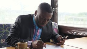 Afro american businessman is filling documets in summer tent cafe looking in smartphone. Black guy is making paperwork. Afro american businessman is filling stock footage