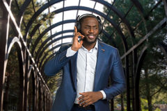 Afro american businessman with headphones outdoors. Black man in formal wear listening to music and enjoying a beat. Dark skinned man smiling with headset Royalty Free Stock Image