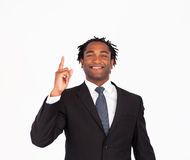 Afro-american businessman pointing upwards. Friendly afro-american businessman pointing upwards Stock Images