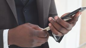 Afro-american businessman reading emails on his smartphone and texting answers. Slow motion stock footage