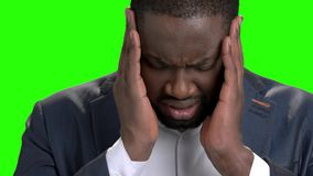 Afro american businessman with strong headache. Young dark-skinned man in formal wear suffering from terrible headache on green screen close up stock video