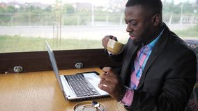 Afro american businessman is typing a message on laptop and drinks cup of coffee. Afro american businessman is typing a message on laptop sitting in summer cafe stock video