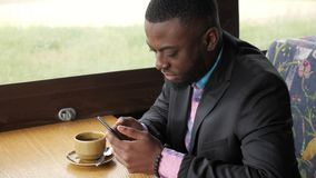 Afro american businessman is typing a message on smartphone sitting in cafe. Afro american businessman is browsing smartphone sitting in cafe. He is typing a stock footage
