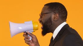 Afro-American businessman using megaphone to spread information, trade news. Stock footage stock video footage