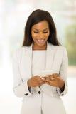 Afro american career woman. Beautiful young afro american career woman using cell phone Royalty Free Stock Photos