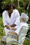 Afro-american caregiver taking care of a disabled senior woman. Afro-american caregiver talking to disabled senior women outdoors Stock Images