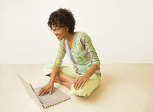 Afro-American Casual Woman on Laptop. African American young woman in bright green print top sitting cross-leg on floor with laptop computer Royalty Free Stock Images