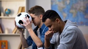 Afro-american and caucasian guys disappointed with football team losing match
