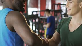 Afro-american and caucasian men shaking hands in gym, international friendship. Stock footage stock video