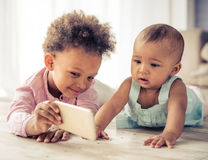 Afro American children. Beautiful little Afro American girls are playing on floor at home. Older girl is showing a smartphone her baby sister Stock Image