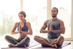 Afro American couple doing yoga. Beautiful Afro American couple in sports clothes is meditating sitting in lotus position on mat while doing yoga royalty free stock photo