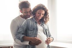 Afro American couple. Handsome Afro American men and his beautiful pregnant wife are hugging and smiling while standing near the window at home Stock Photography