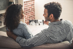 Afro American couple. Handsome Afro American men and his beautiful pregnant wife are watching sonogram and smiling while spending time together at home Stock Photography
