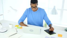 Afro-American creative designer working with graphic tablet on laptop stock footage