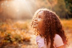 Afro american cute little girl with curly hair receives miracle sun rays from the sky. Afro american happiness little girl with curly hair receives miracle sun stock image