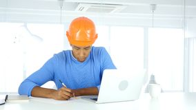 Afro-American Engineer Writing in Office, Documentation royalty free stock images