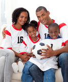 Afro-american family holding a soccer ball. Smiling Afro-american family holding a soccer ball on the sofa Royalty Free Stock Photos