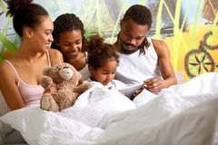 Afro American family together with child in bed stock photos