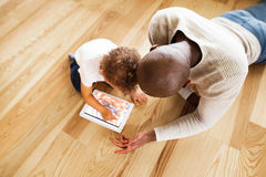 Afro-american father with little daughter with tablet at home. Young afro-american father at home with his cute little mixed-race daughter lying on the floor Stock Image