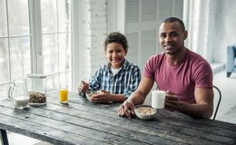 Father and son. Afro American father and son in casual clothes are looking at camera and smiling while having breakfast together at home stock photos