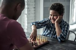 Father and son. Afro American father and son in casual clothes are playing chess while spending time together at home, boy is smiling royalty free stock photography
