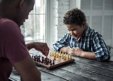 Father and son. Afro American father and son in casual clothes are playing chess while spending time together at home royalty free stock image