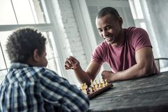 Father and son. Afro American father and son in casual clothes are playing chess while spending time together at home, men is smiling stock photo