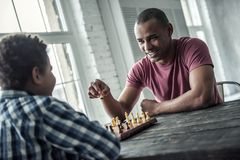 Father and son. Afro American father and son in casual clothes are playing chess while spending time together at home, men is smiling stock photos