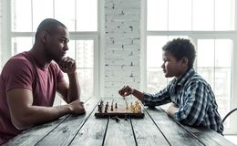 Father and son. Afro American father and son in casual clothes are playing chess while spending time together at home, side view royalty free stock photo