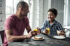 Father and son. Afro American father and son in casual clothes are talking and smiling while eating at the wooden table together at home royalty free stock images