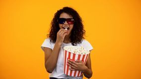 Afro-American female in 3d glasses eating popcorn and watching comedy show. Stock photo royalty free stock image