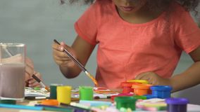 Afro-American female kid painting a picture at art club, preschool education. Stock footage stock video