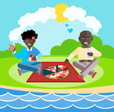 Afro-American friends at the picnic. Two man Afro-American friends at the picnic eating pizza. Picnic on the beach. Summer picnic. Aframerican couple eating Stock Photos