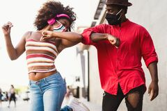Afro American friends wearing face protective mask doing new social distance greetings bumping elbows