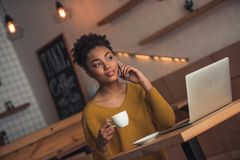 Afro American girl in cafe. Beautiful Afro American girl in casual clothes is talking on the mobile phone, drinking coffee and smiling while working with a royalty free stock photo