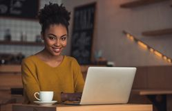 Afro American girl in cafe. Beautiful Afro American girl in casual clothes is using a laptop, looking at camera and smiling while sitting in cafe stock image
