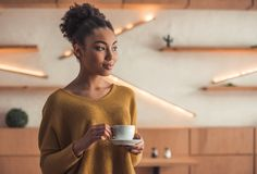 Afro American girl in cafe. Beautiful Afro American girl in casual clothes is drinking coffee, looking away and smiling while resting in cafe royalty free stock image